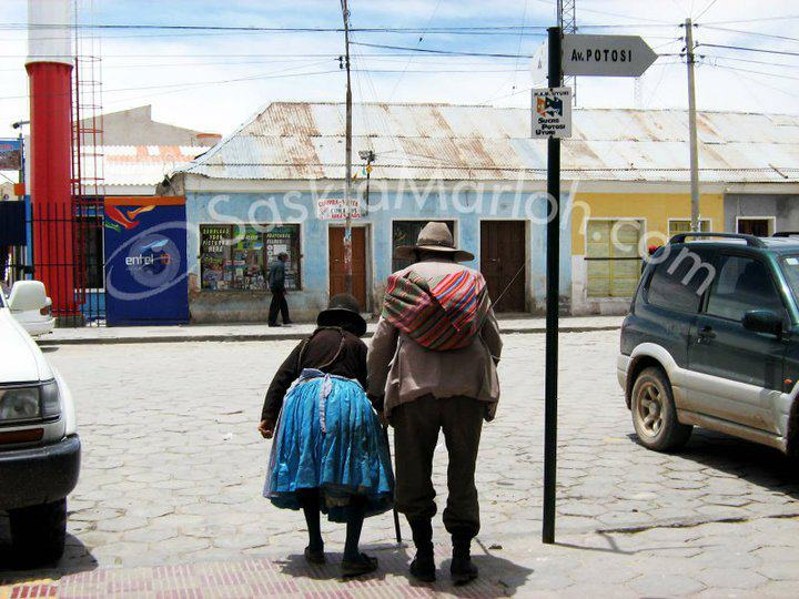 This couple in the streets of Uyuni, Bolivia caught my attention and touched me deeply, they seem both so fragile and so together at the same time. Right at the edge of a wide street, between modern cars, helping each other to cross the street and at the other side advertising for telecomunication. Standing by each side.Chosen by NatGeo in the photo contest 2010